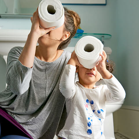 Mother and daughter playing with toilet paper rolls