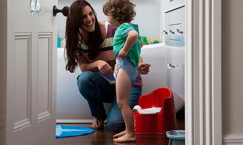 Mother helping little boy with potty training
