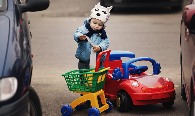 Boy with toy shopping cart