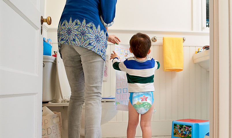 Mother and son potty training in bathroom