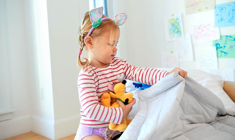 Little girl with pluto doll making her bed