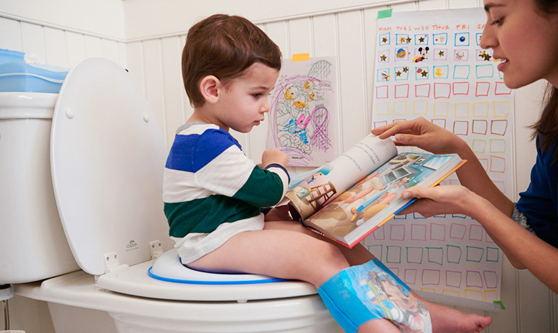 Kid on toilet reading book with mom