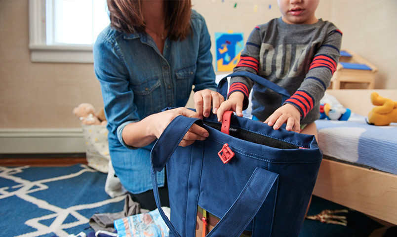 Mom and kid putting stuff in back pack