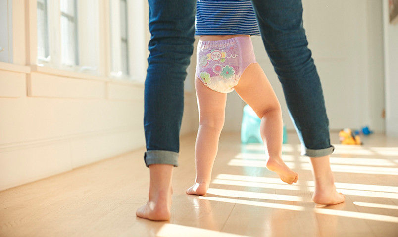 Mom helping kid walk in pink diaper