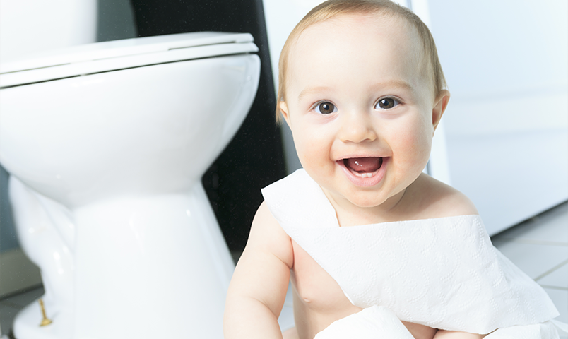 Happy baby playing with toilet paper in bathroom