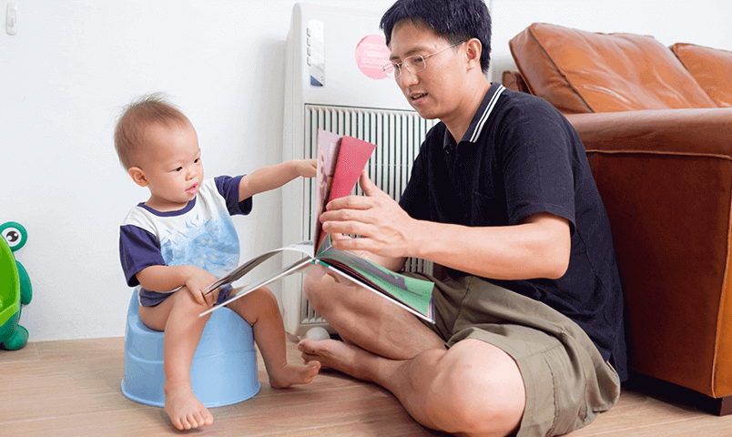 Dad teaching child about potty training with potty book