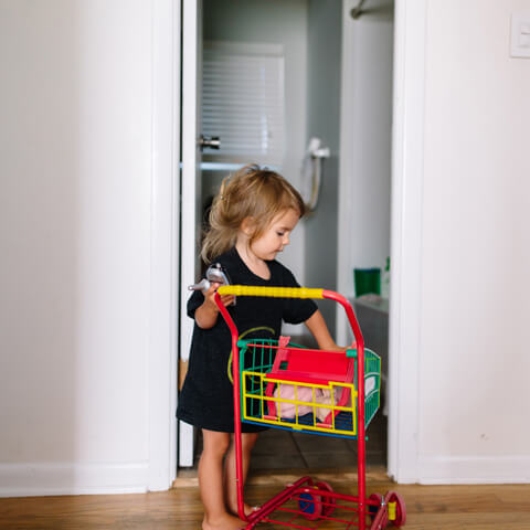 Child with a small shopping cart in the middle of a hallway