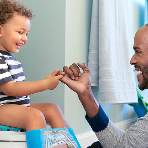 Dad pinky promises son a reward if he uses the potty in the bathroom