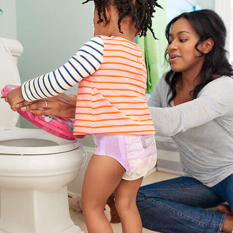 Mom and daughter placing potty seat