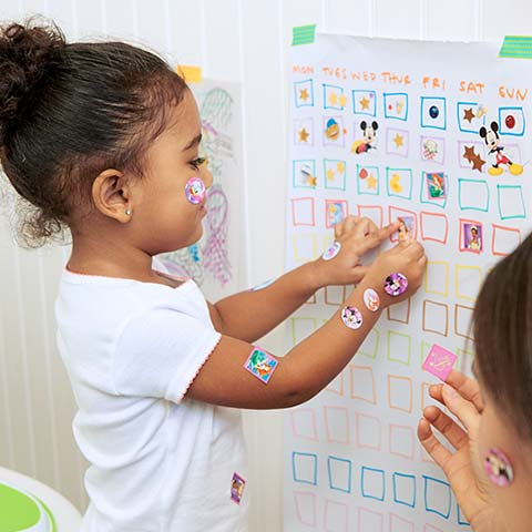 Girl placing stickers on chart