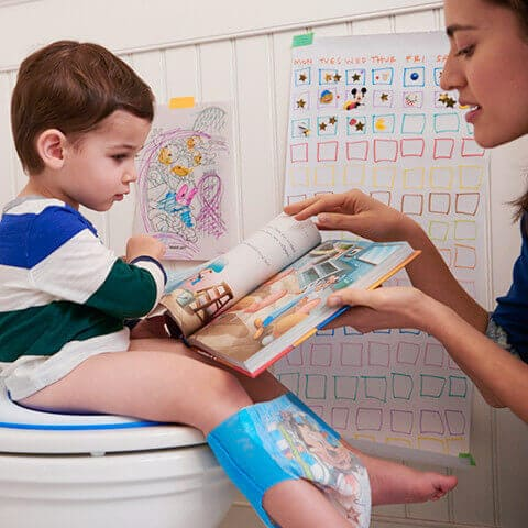 Kid sitting on toilet reading large book