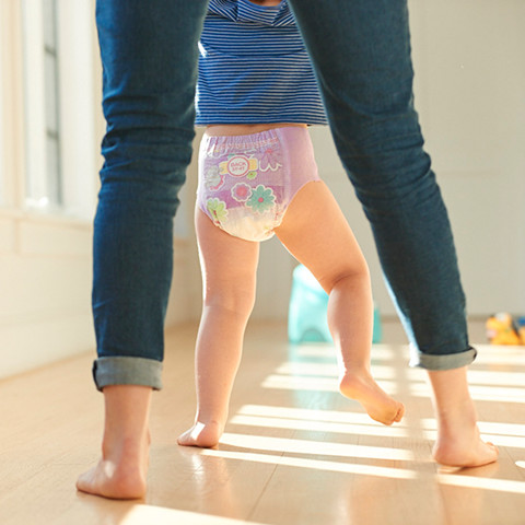 Mom helping kid walk with pink diaper