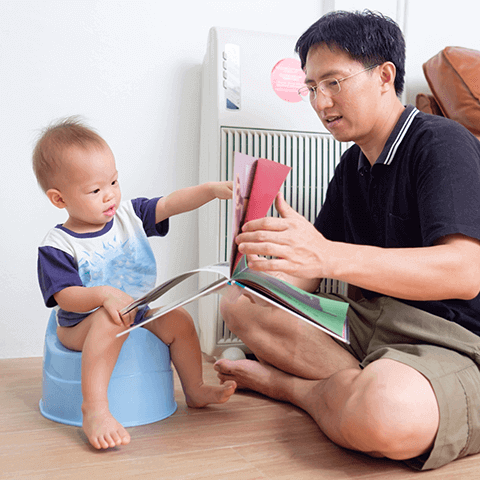 Dad teaching baby using a potty training book