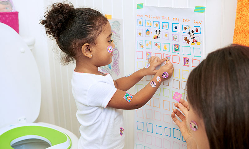 Girl adding stickers to Potty Chart