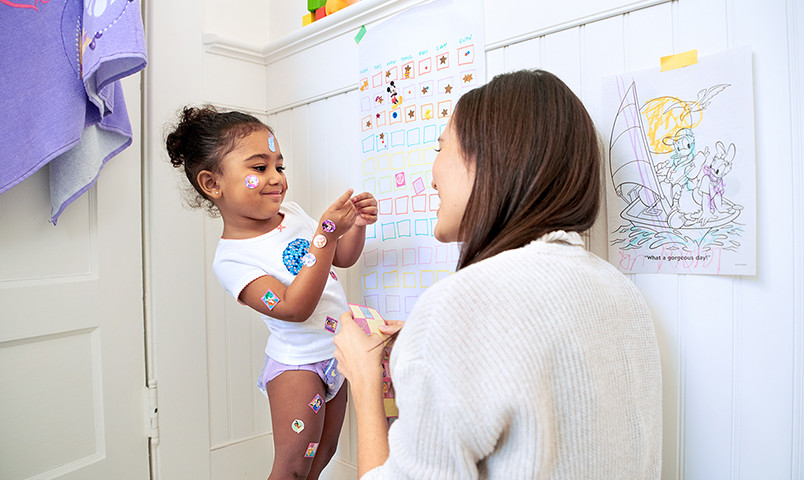 Baby and mom playing with stickers inside bathroom