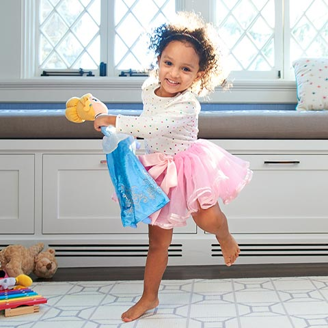 Happy child dancing with Disney Elsa doll