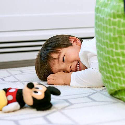 Child plays on the floor with Disney Mickey Mouse